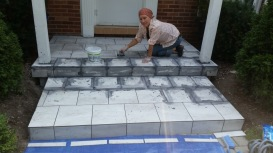Cleaning the excess grout from the tiles lightly