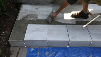 Mortar application on the cement and always back-butter the tile for a solid air-gap free surface